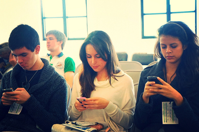 Teens sitting together, playing on social media